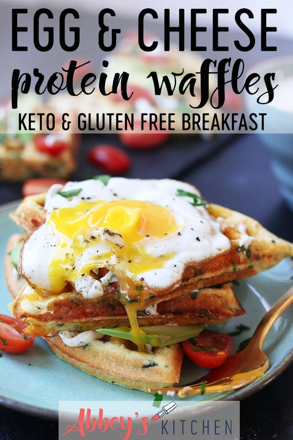 Egg and cheese savory protein waffles piled on a turquoise plate topped with a fried egg.