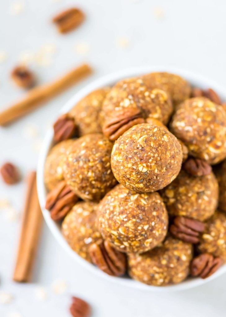 Pumpkin energy balls in a white bowl with pecans and cinnamon stick garnish from family meal plan.