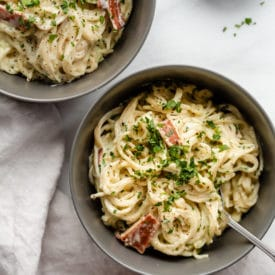 Two grey bowls filled with pasta carbonara.