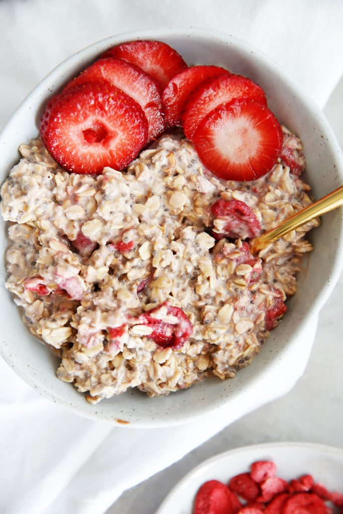 Strawberry overnight oats in a white bowl with a gold spoon from family meal plan.