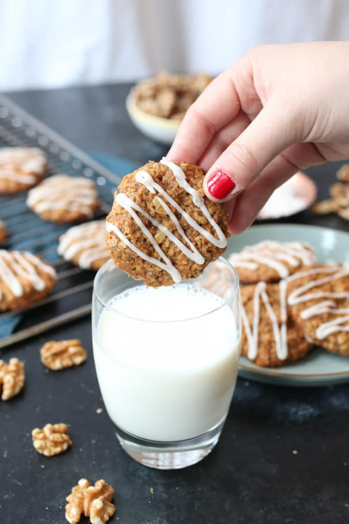 Hands dipping vegan carrot cake lactation cookies in a glass of milk.