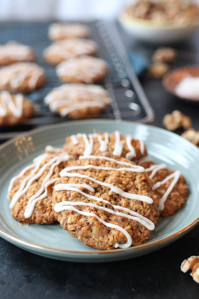 Pile of vegan carrot cake lactation cookies on a teal plate with cookies on a rack in the background.