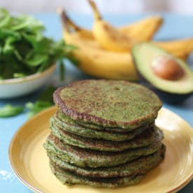 Stack of spinach and avocado green pancakes on a yellow plate.
