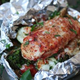 Baked chicken parmesan foil pack dinner with vegetables.