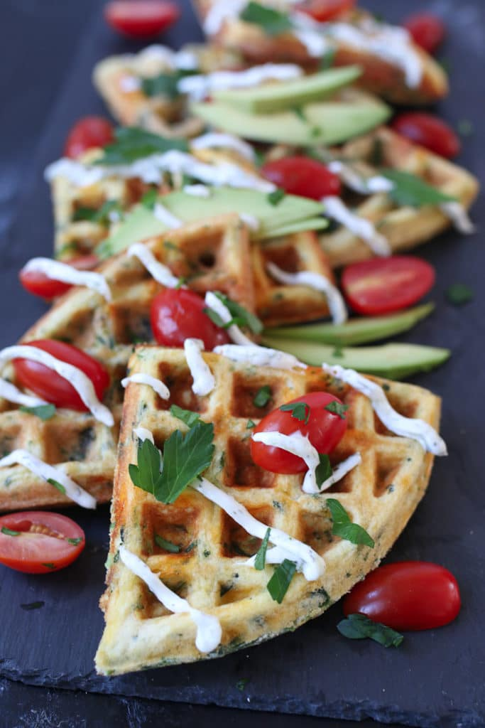 a platter of egg and cheese waffles topped with cherry tomato and parsley