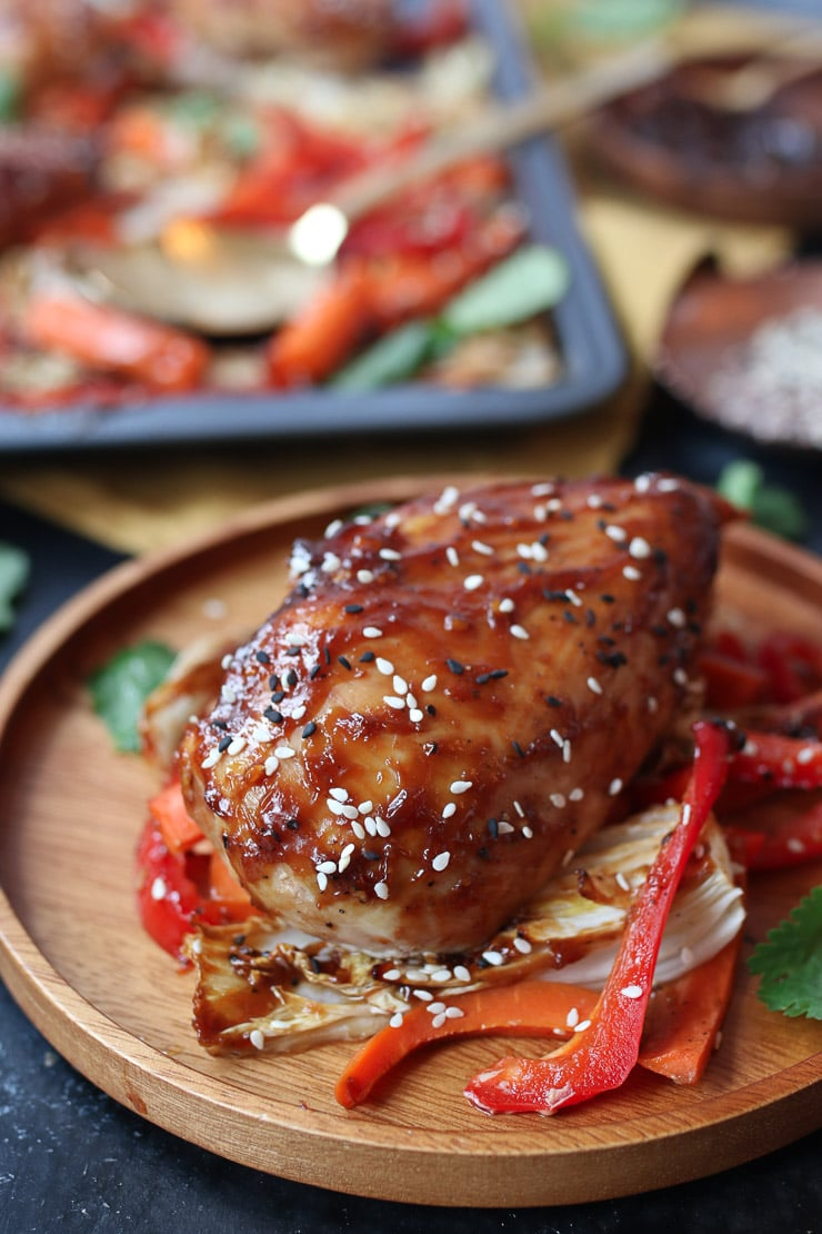 Baked sweet and sour chicken on a bed of cabbage and peppers on a wooden plate.