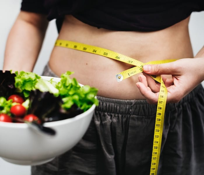 Person measuring their weight circumferance with measuring tape holding a bowl of salad.