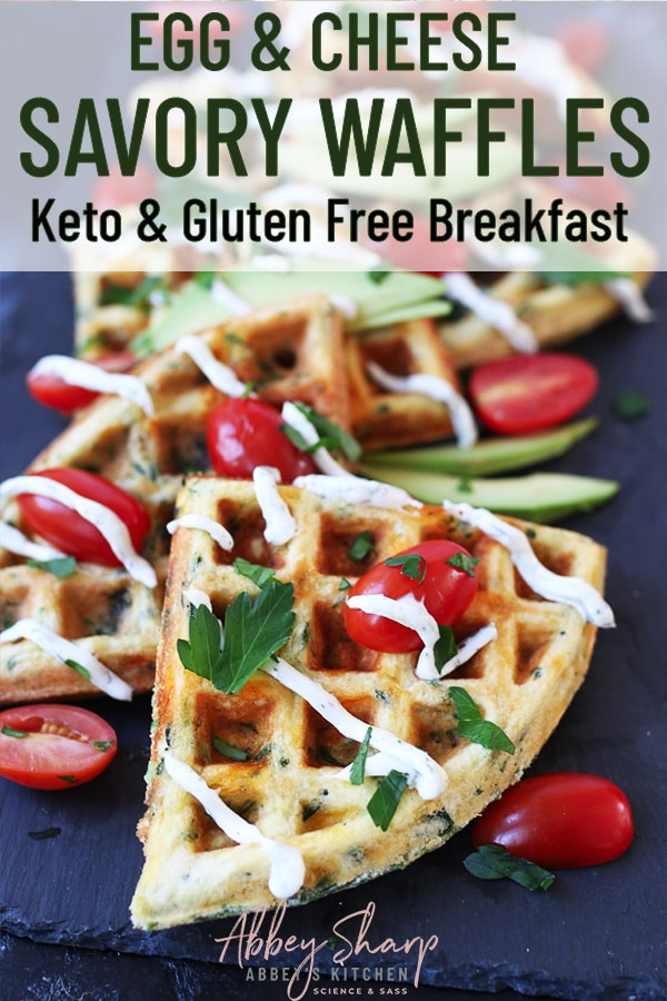 pinterest image of a grey platter featuring multiple egg and cheese savoury brunch waffles garnished with tomatoes and fresh herbs with text overlay