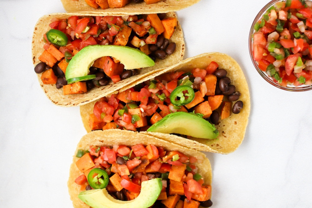Three sweet potato tacos on a white background topped with a slice of avocado from family meal plan.