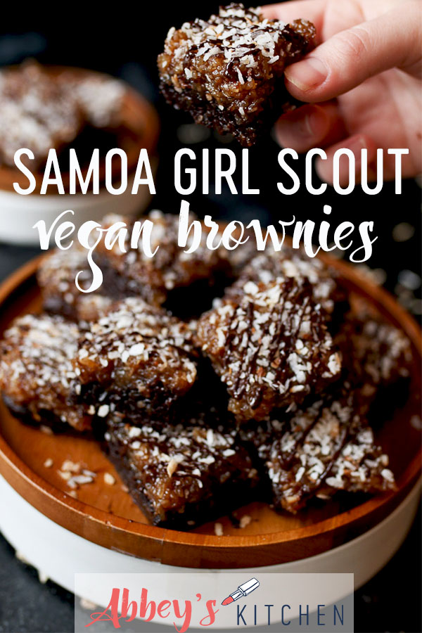 Samoa girl scout vegan brownies on a wooden plate topped with chocolate and coconut.