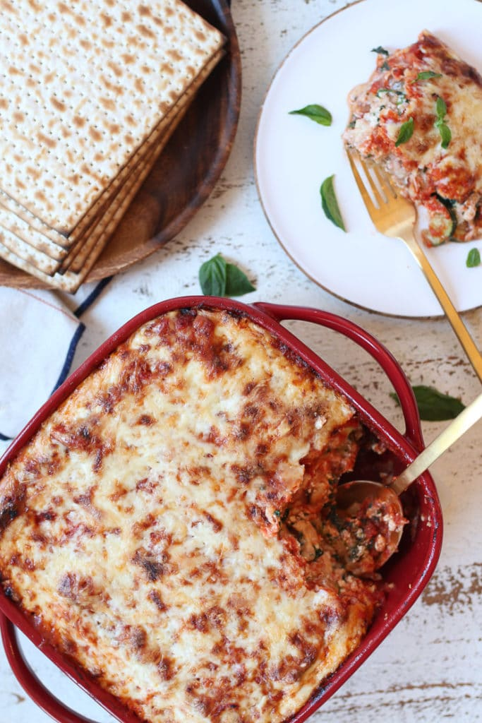 Passover Matzo Lasagna in a red casserole dish next to a serving on a plate.