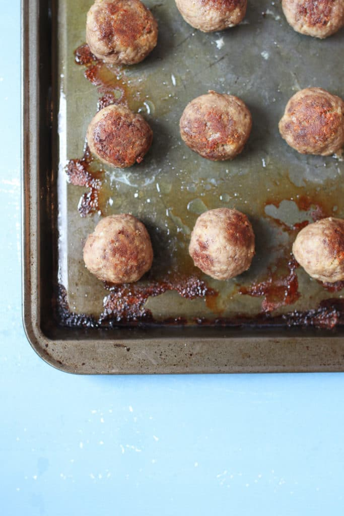 Hummus baby meatballs on an aluminum pan.