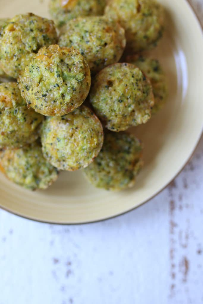Pile of mini broccoli and cheese egg muffins on a yellow plate.