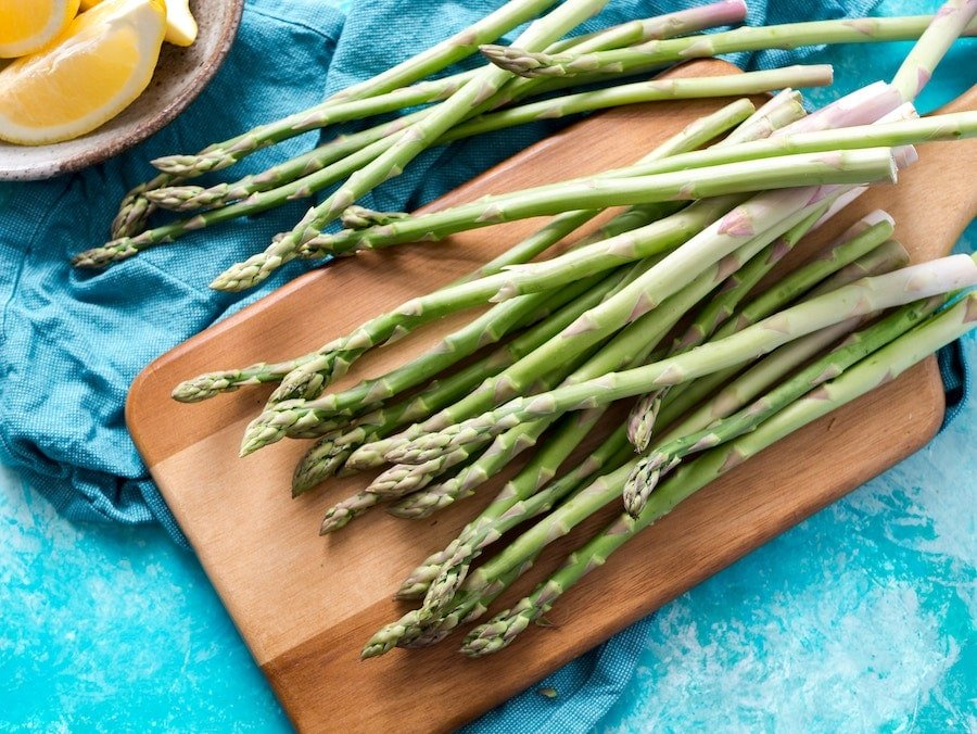 A pile of fresh asparagus on a cutting board.