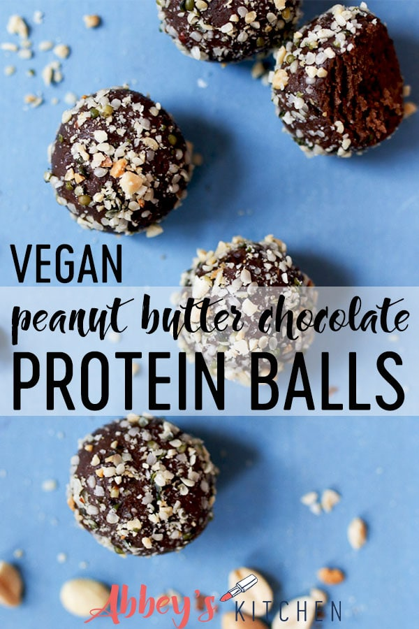 Peanut butter chocolate protein balls scattered on a blue background.