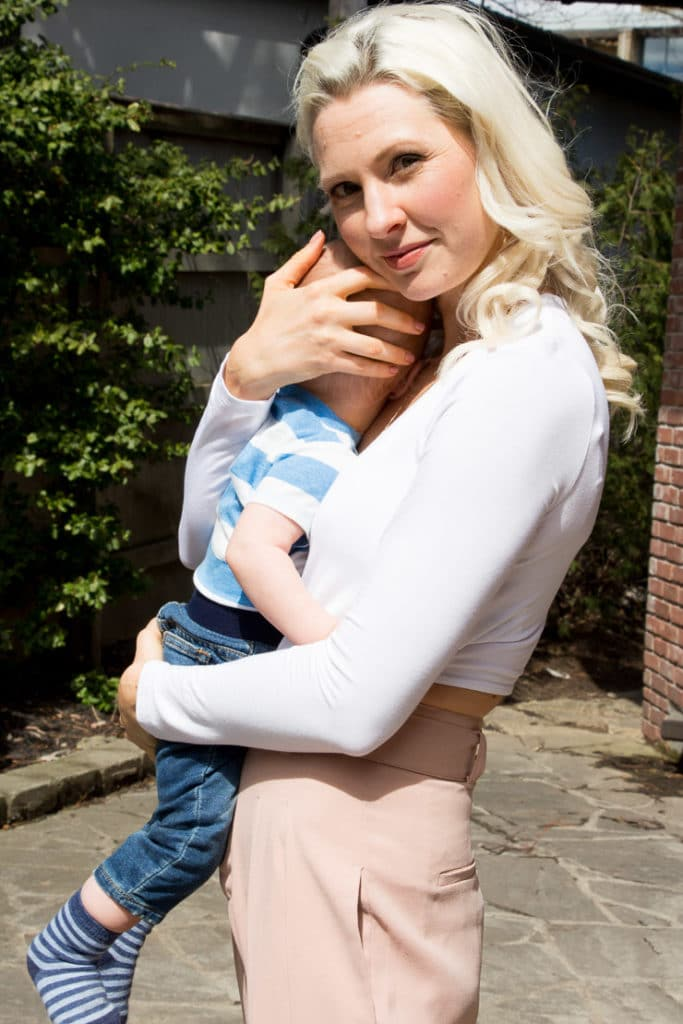 Women holding her baby boy in her arms.