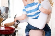 Women holding her baby while cooking.