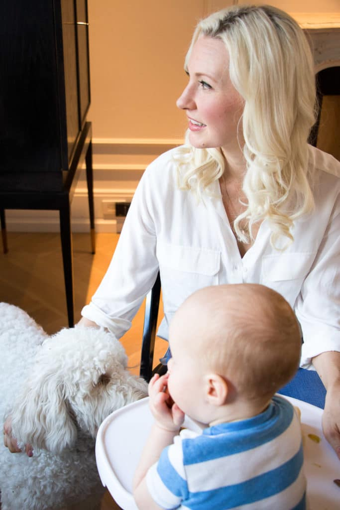 Women sitting next to her baby in a high chair and her dog.