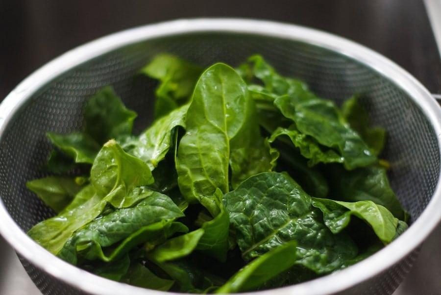 Colander with fresh spinach.