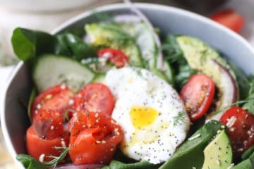 Keto salad topped with poached egg, smoked salmon and avocadoes in a bowl.