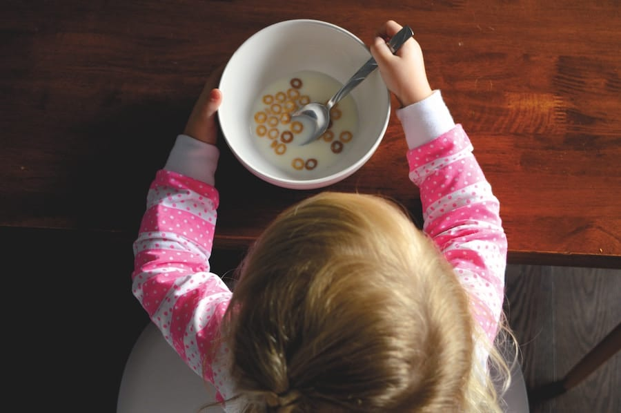 Little girl eating cereal in a bowl.
