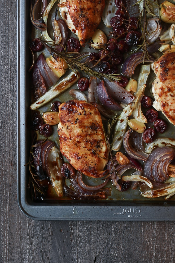 Sheet pan balsamic chicken on a sheet pan with roasted grapes and veggies.