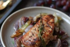 Baked rosemary chicken on a plate with roasted onions and grapes.