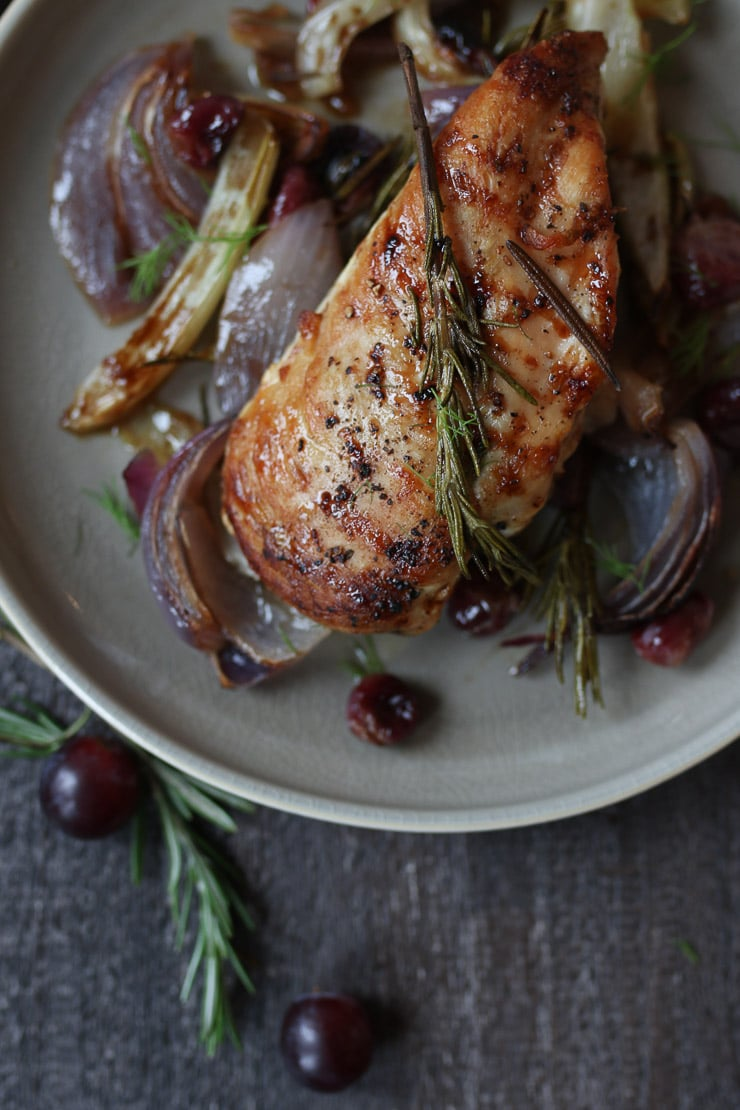 Baked balsamic chicken on a plate with roasted onions and grapes.