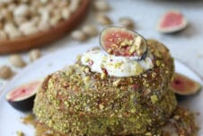 Pistachio crusted french toast on a white plate topped with yogurt and figs.