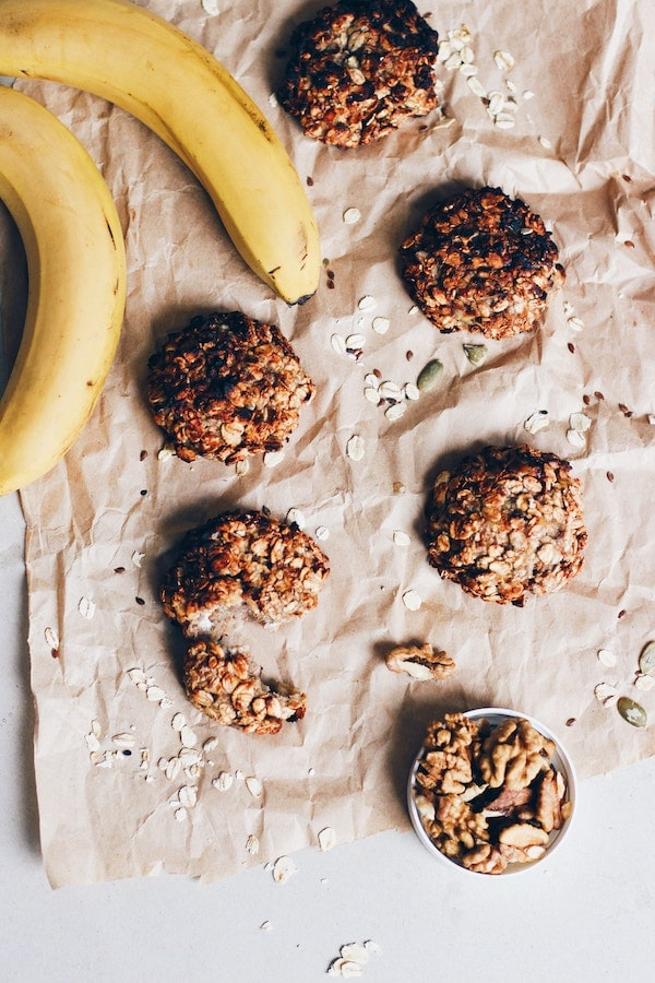 Granola cookies on brown paper next to bananas.