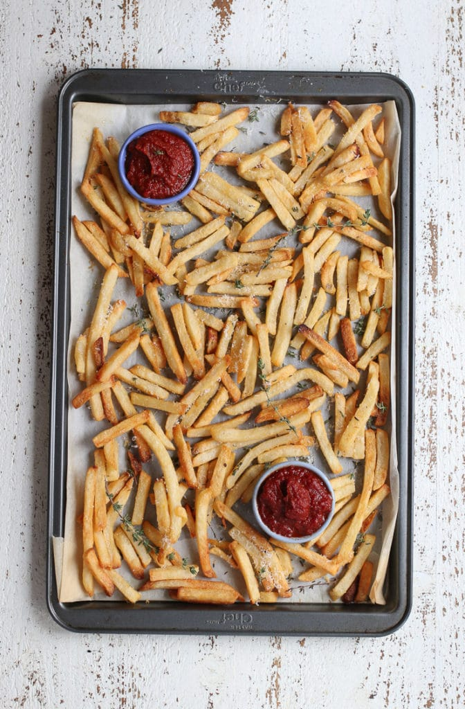 A tray of french fries with two small bowls of homemade ketchup.