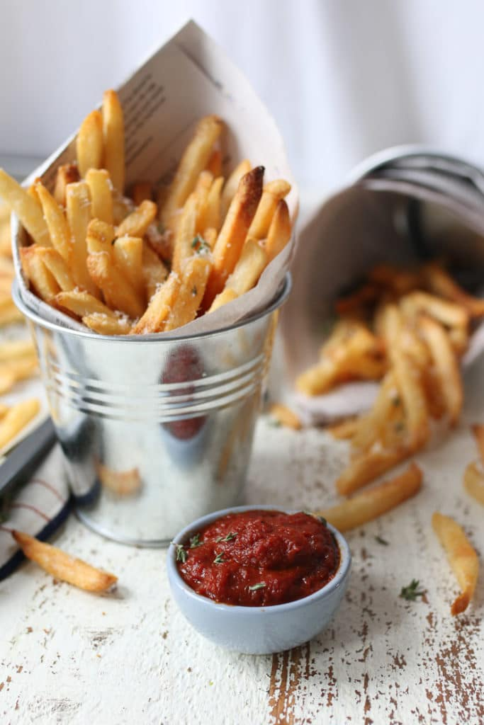 Fries in a bucket next to a bowl of homemade ketchup.