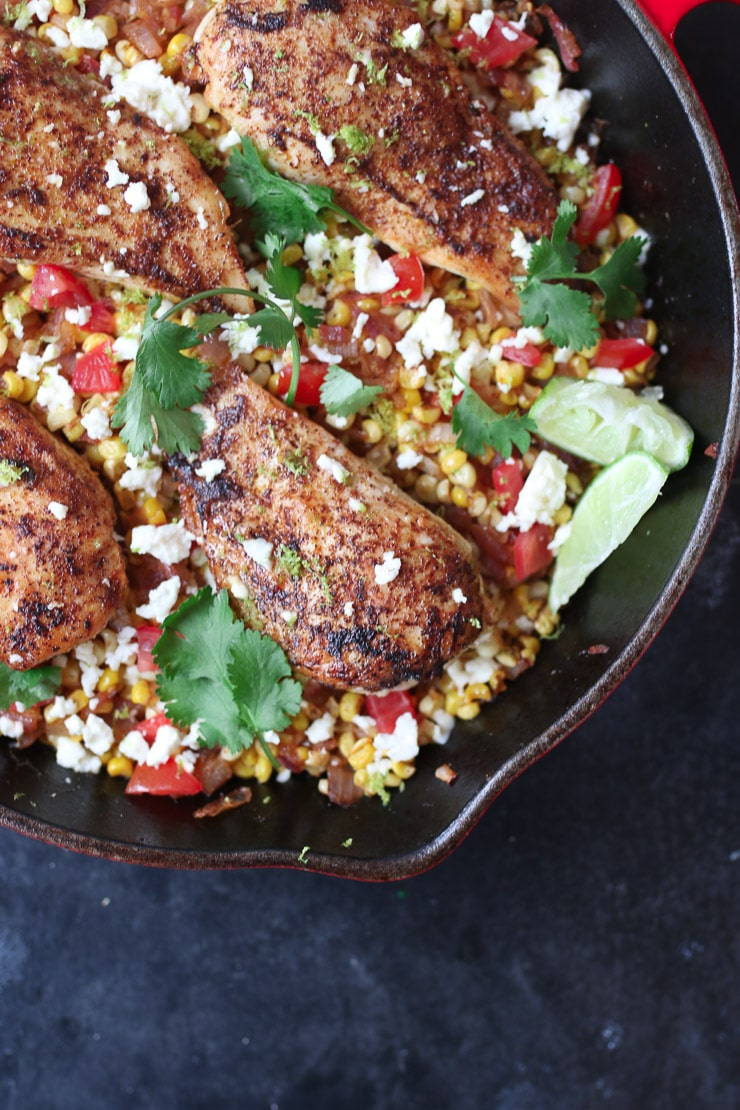 Mexican chicken and corn in one pan topped with cilantro and lime wedges.