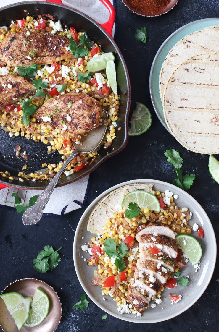 spiced chicken and corn in a pan next to a serving on a plate.