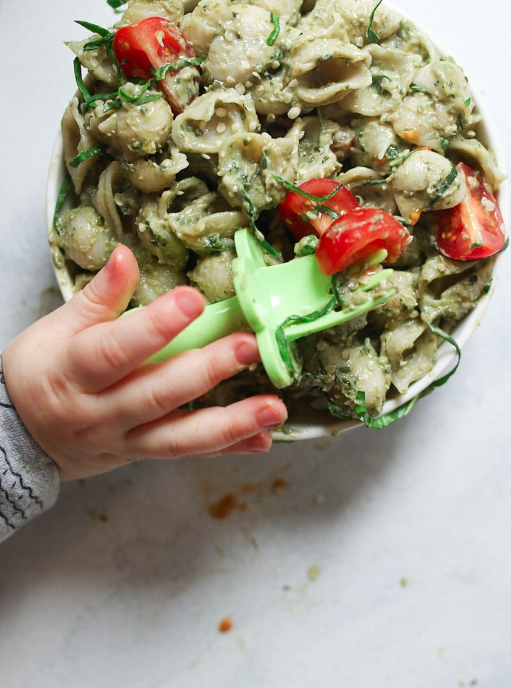 Baby's hand holding a fork over a bowl of avocado pasta.