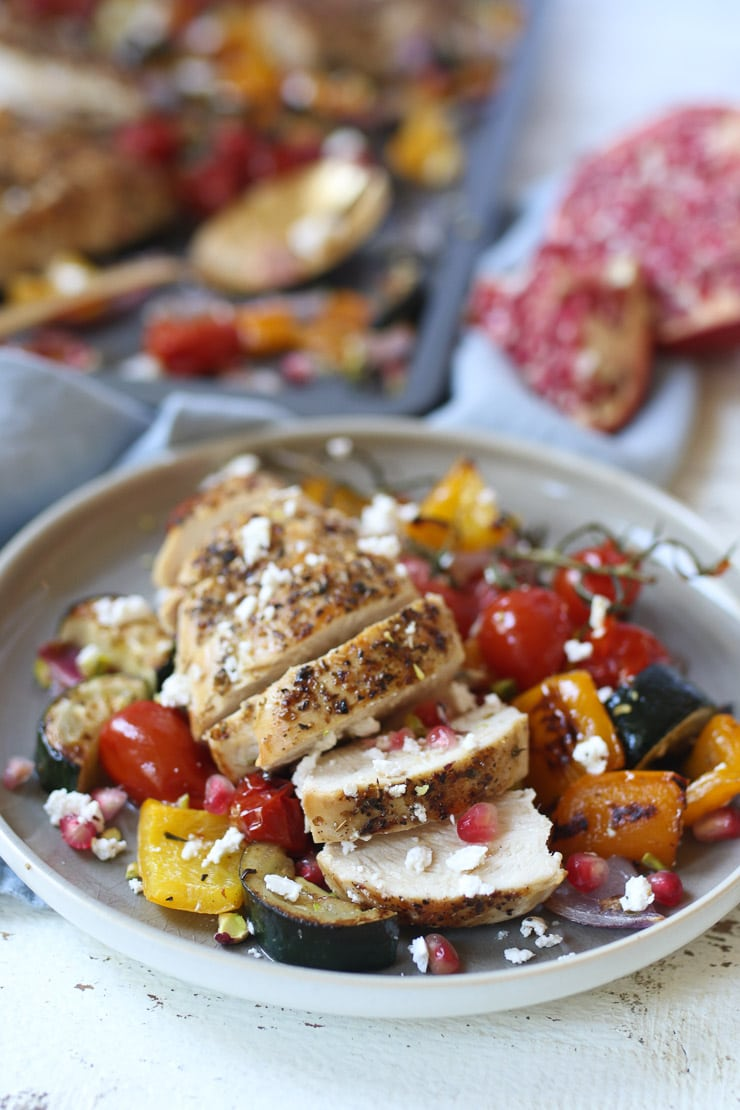 Greek chicken and vegetables on a grey plate.