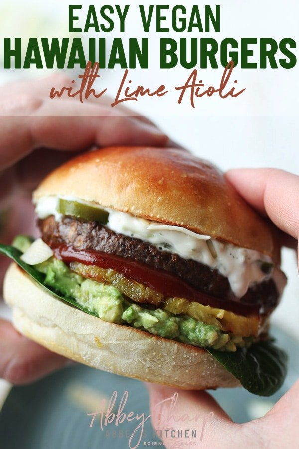 pinterest image of two hands holding a vegan hawaiian burger with homemade lime aioli garnished with avocado, vegetables, and pineapple on a hamburger bun with text overlay