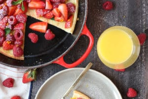 Slice of dutch baby on a plate topped with berries next to a pan.