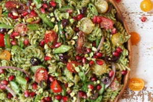 Pistachio parlsey vegan pesto pasta salad on a wooden plate with cherry tomatoes and pomegranates.