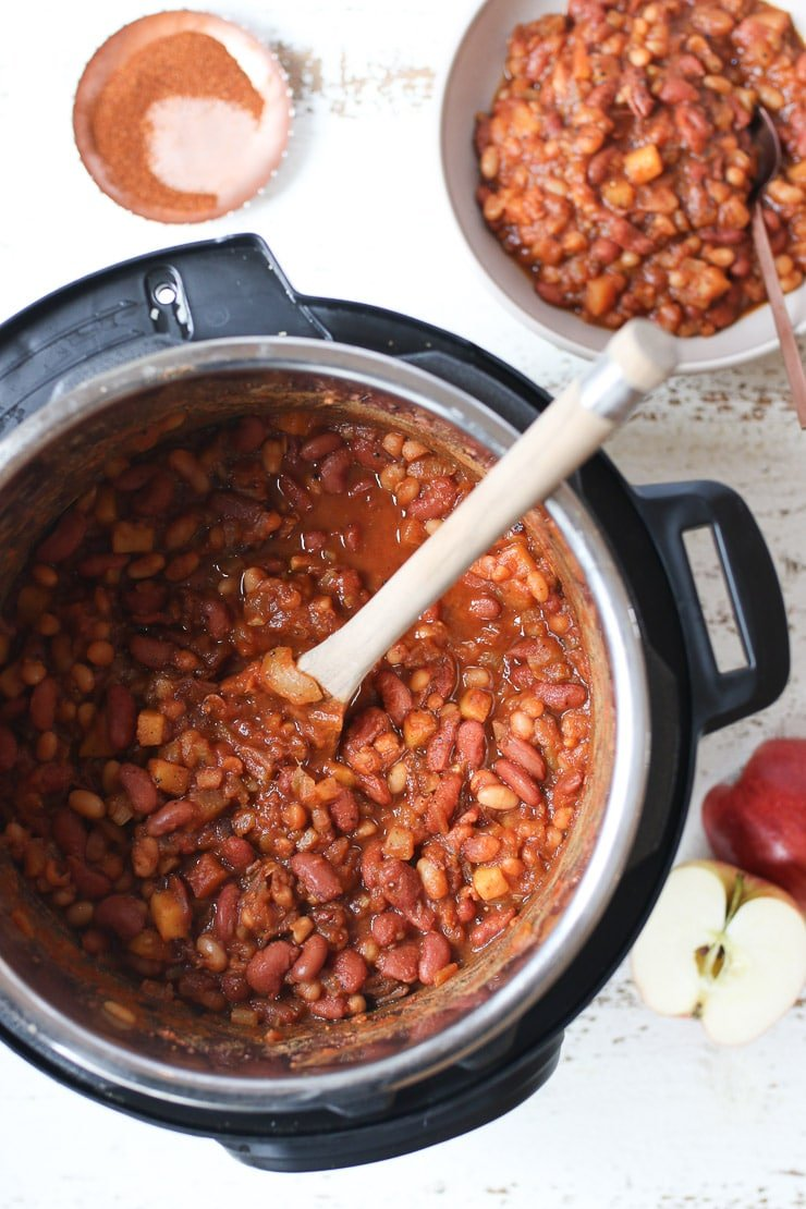 Baked beans in an instant pot with a wooden spoon