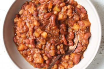 Close up of baked beans in a bowl with a spoon.