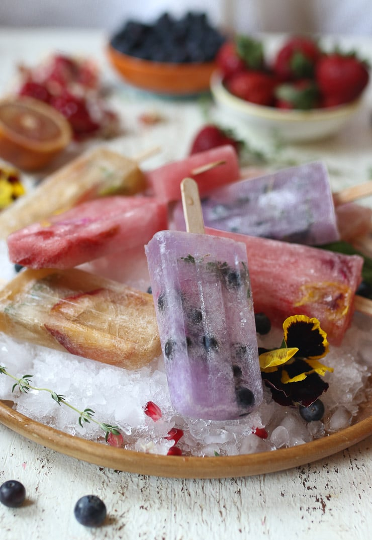 Homemade popsicles on a bed of ice on a wooden plate.