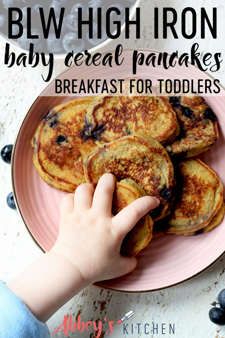 pinterest image of baby hand reaching for cereal protein pancakes on a pink plate with text overlay