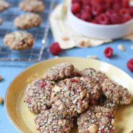 Cookies on a yellow plate next to a bowl of raspberries.