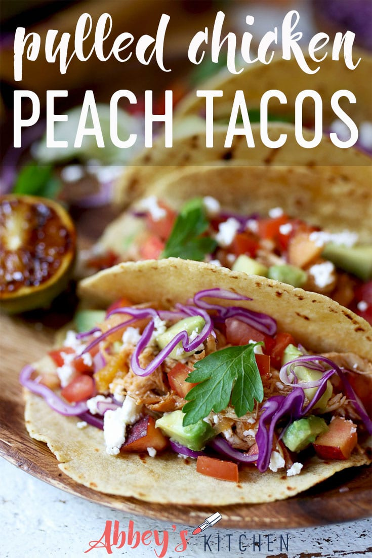 Pulled chicken tacos topped with peaches, slaw and cilantro.