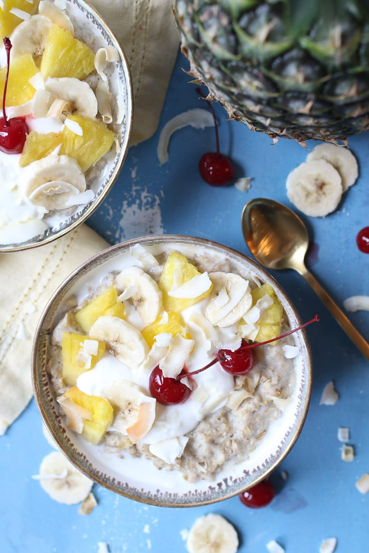 Bowl of oatmeal topped with pineapple, cherries and yogurt.