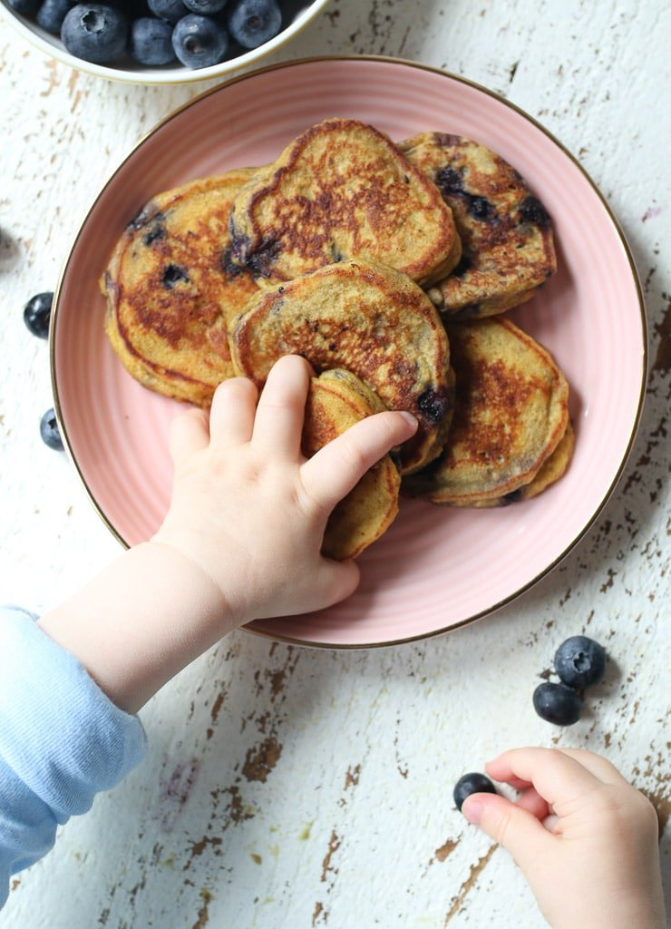 Baby's hand grabbing a baby pancake and a blueberry.