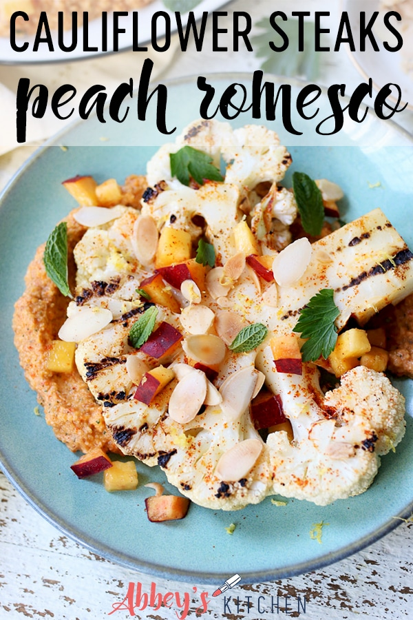 pinterest image of grilled cauliflower steaks with a peach romesco sauce on a teal plate with text overlay