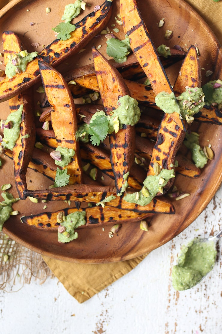 BBQ sweet potato on a wooden plate with avocado lime sauce