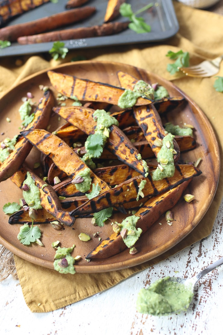Sweet potato wedges made on the grill on a wooden plate with avocado lime sauce on top